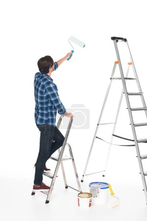 rear view of man standing on ladder with roller paint isolated on white background