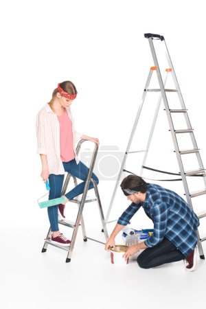 Photo for Man opening paint tin and girlfriend standing near on ladder with paint roller isolated on white background - Royalty Free Image