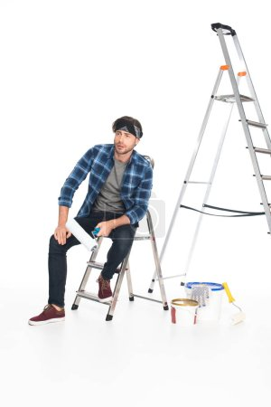 man in headband sitting on ladder with paint roller isolated on white background