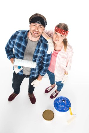 high angle view of couple in headbands and protective gloves standing with paint roller isolated on white background