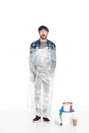 shocked young man in polyethylene cover standing near paint tins, paint roller and coffee cup isolated on white background