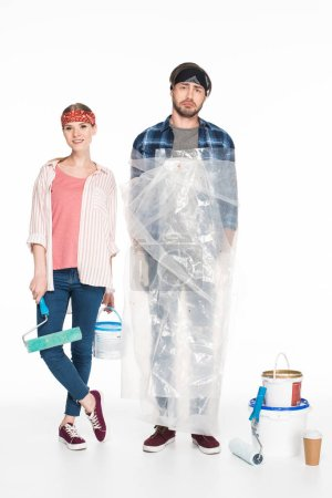 Photo for Smiling woman with paint tin and paint roller standing with boyfriend in polyethylene cover near painting tools and coffee cup isolated on white background - Royalty Free Image