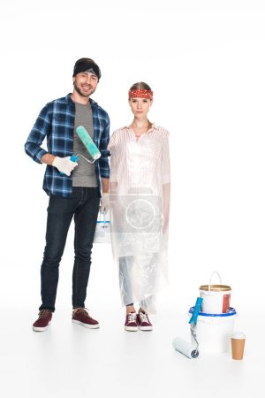 Photo for Young smiling man with paint roller standing near girlfriend in polyethylene cover and painting tools with paper cup of coffee on floor isolated on white background - Royalty Free Image
