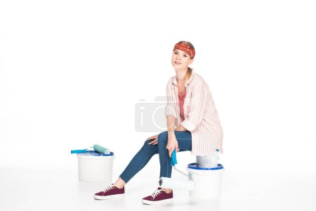 woman in headband sitting with paint roller on paint tins isolated on white background