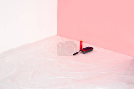 close up view of bottle, roller tray and paint roller in front of painted wall