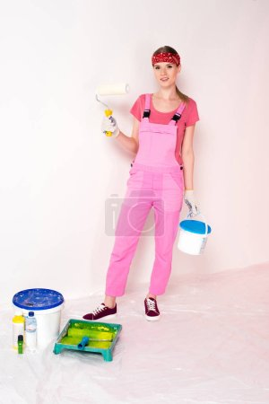 young woman in headband and working overall standing with paint roller and paint tin