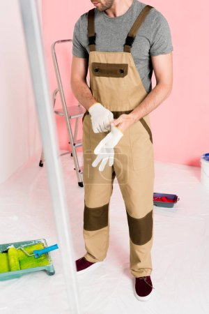 cropped shot of man in working overall putting on protective gloves in room with ladders and paint tin
