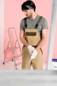 young man in working overall putting on protective gloves in room with ladders and paint tin