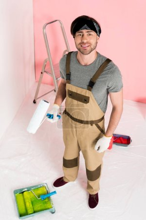 high angle view of man in protective gloves and working overall holding paint roller