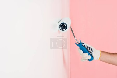 partial view of man in protective glove painting wall in white by paint roller