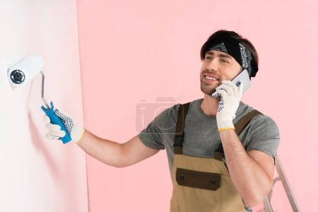 smiling man in protective gloves and working overall talking on smartphone and painting wall by paint roller
