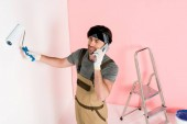 high angle view of man in protective gloves and working overall talking on smartphone and painting wall by paint roller