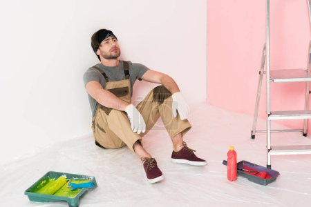 man in headband and working overall resting on floor near roller trays with paint rollers, bottle and ladder