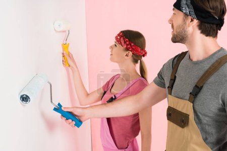 side view of young couple in working overalls painting wall by paint rollers