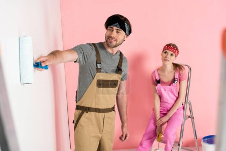 woman in working overall sitting on ladder and watching boyfriend painting wall by paint roller