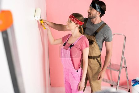 side view of man in working overall teaching girlfriend painting wall by paint roller