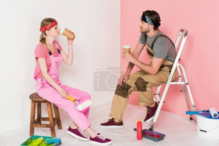 side view of couple in working overalls sitting and drinking coffee in room with painting tools
