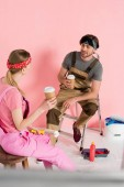 "Постер, картина, фотообои ""женщина на стул с бумаги чашки кофе и бойфренд, сидя на лестнице с чашки кофе в комнате с инструменты рисования"""