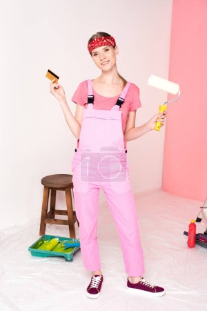 smiling young woman in working overall holding credit card and paint roller