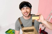 smiling man in headband and working overall holding credit card