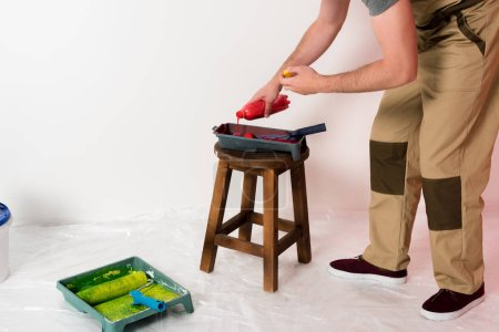 cropped shot of man in working overall pouring paint from bottle into roller tray on chair