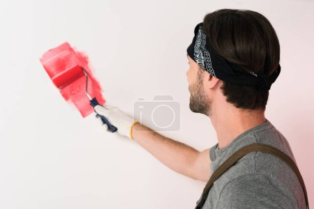 back view of man in headband painting wall in red by paint roller