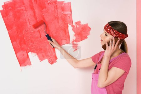 side view of young woman in headband and working overall talking on smartphone and painting wall in red by paint roller