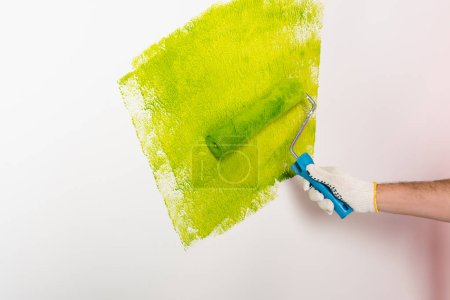 cropped image of man in protective glove painting wall by paint roller