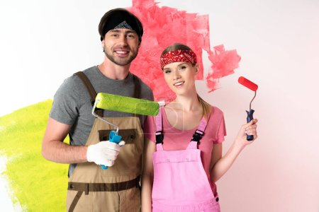 Photo for Young couple in working overalls and headbands standing with paint rollers in front of painted wall - Royalty Free Image