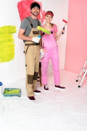 smiling young couple in working overalls standing with paint rollers