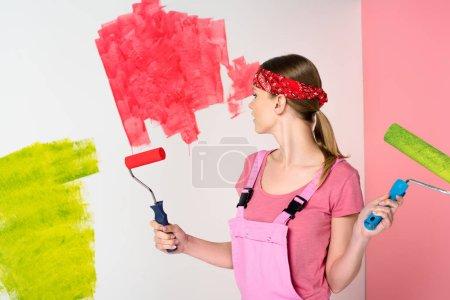 Photo pour Jeune femme en bandeau et travail global tenant de rouleaux à peindre en face du mur peint - image libre de droit