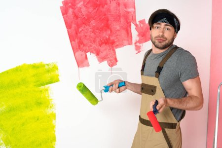 young man in working overall holding paint rollers and doing shrug gesture in front of painted wall