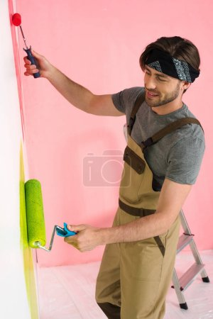 smiling man in working overall painting wall by two paint rollers