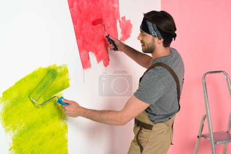 side view of smiling man in working overall painting wall by two paint rollers