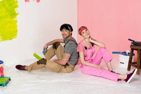 Photo pour Fatigué de jeune couple en salopettes de travail assis sur sol entouré d'outils de peinture - image libre de droit