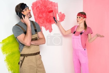 dissatisfied young woman painting wall and gesturing to smiling boyfriend talking on smartphone
