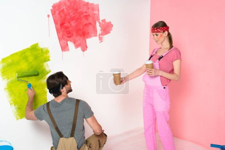 young woman in working overall giving coffee cup to boyfriend while he painting wall