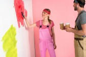 young woman standing with paper cups of coffee and girlfriend painting wall by paint roller