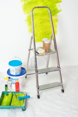 close up view of paint tins, bottles, roller tray with paint roller, ladder with protective gloves and paper cups of coffee