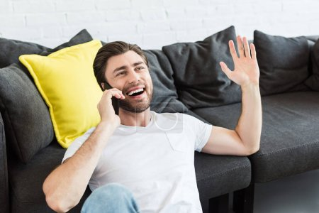 young man gesturing by hand and talking on smartphone near couch at home