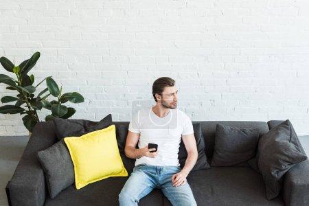 Photo pour Vue grand angle du jeune homme assis sur le canapé avec smartphone à la main à la maison - image libre de droit