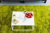 elevated view of table with laptop, coffee cups, apples in bowl, books, eyeglasses and plant at home