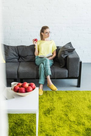 young woman in eyeglasses reading book and holding apple on sofa near table with coffee, apples and laptop at home