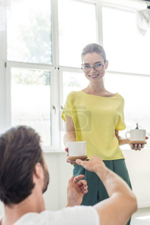 happy young woman in eyeglasses giving coffee cup to boyfriend