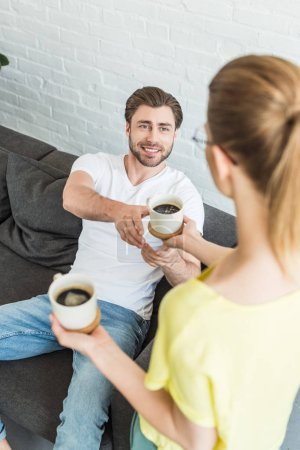 rear view of woman giving coffee cup to smiling boyfriend sitting on sofa at home