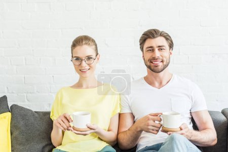 portrait of smiling young couple holding cups with coffee and sitting on couch at home