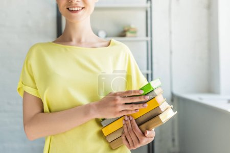 cropped image of smiling young woman holding stack of books
