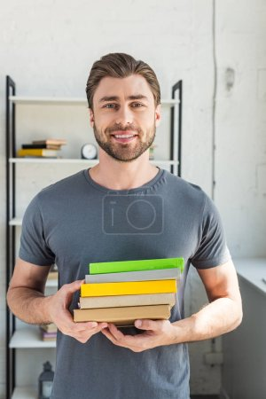 portrait of smiling man standing with stack of books at home