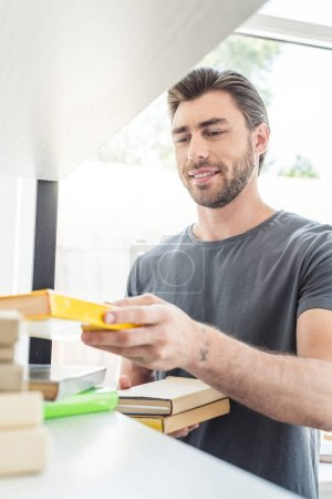 young smiling man putting books on shelves at home