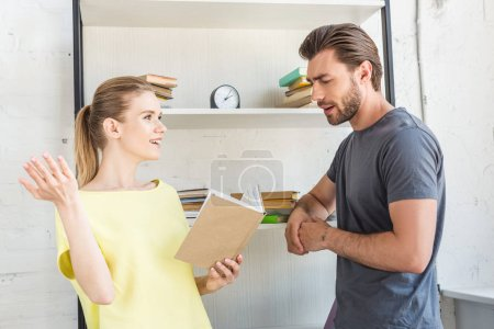 side view of smiling woman gesturing by hand and reading book to boyfriend
